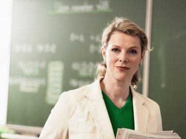 Lehrerin steht an Tafel in der Schule